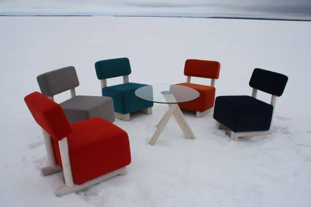 A circle of upholstered chairs sits on the frozen Oulu lake. There are no people in the picture.