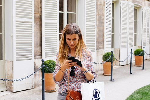 A woman with a shopping bag over her arm stands in front of a building while holding up her smartphone. She's taking a few minutes to review her Finnish vocabulary flashcards with an app.