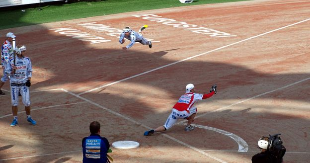 Two teams compete in a Finnish game similar to American baseball on a field that looks somewhat like a baseball diamond.