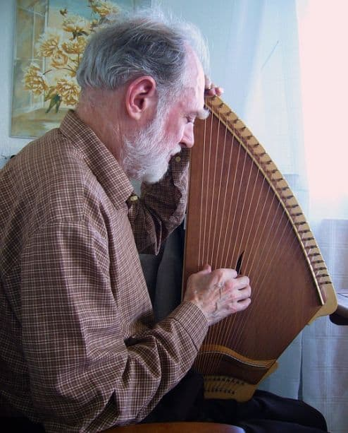 A man is seated while playing the kantele, a wooden stringed instrument (similar to a zither) that's traditional in Finland.