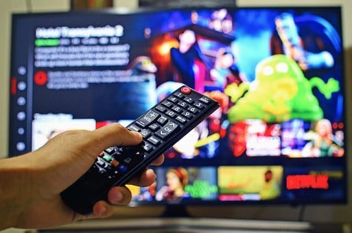 A person holding a remote control looks at a variety of choices on a streaming service, such as Netflix.