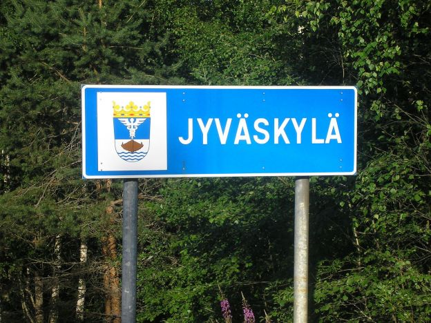 A blue city limits sign for Jyväskylä, Finland stands in front of a group of evergreen trees. The sign also displays Jyväskylä's coat of arms, which features water, a ship, and a Caduceus, topped with a crown.