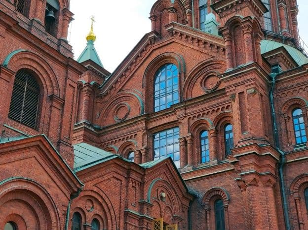 The imposing façade of Uspenski Cathedral is covered in red brick a with light green roof. The architecture is a Romanesque style, with rounded arches surrounding windows and doors.