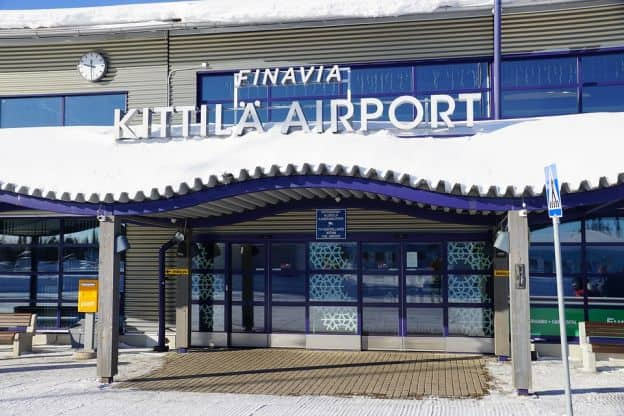 An entrance to Kittilä Airport in Finland, with snow on the roof and sidewalk of the building.