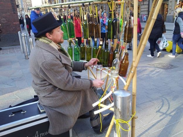 A man dressed in an overcoat, with a hat and scarf, sits in back of an array of beer bottles suspended from a curved frame. These comprise his musical instrument.