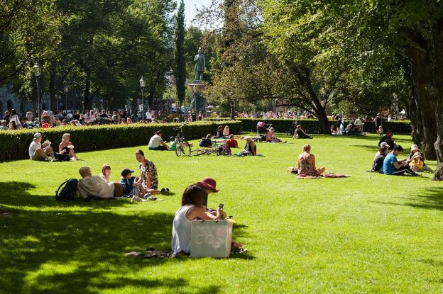 Many people laze on the grass to enjoy spring-like weather at a popular park in Helsinki.