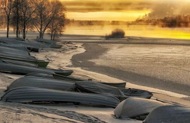 Inverted rowboats line the shore as the sun sets on a beach in Finland. There is snow on the sand.