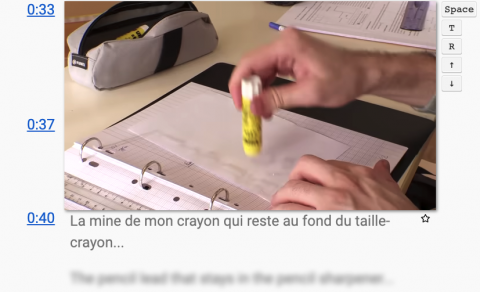 A hand with a glue stick glueing paper in a binder. Time stamps to the right of the image with French subtitles below. English words blurred out below the subtitles.