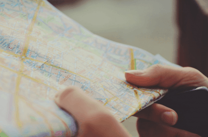 Photo of a road map being held in someone's hands.