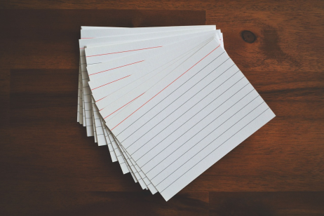 A pile of blank flashcards spread out on a wood desk.