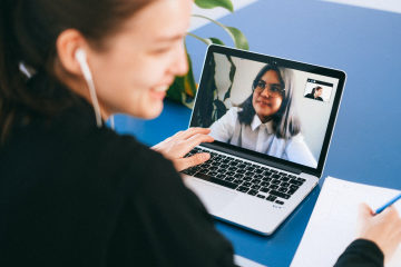 A language tutor and student speak on a video call through a laptop screen.