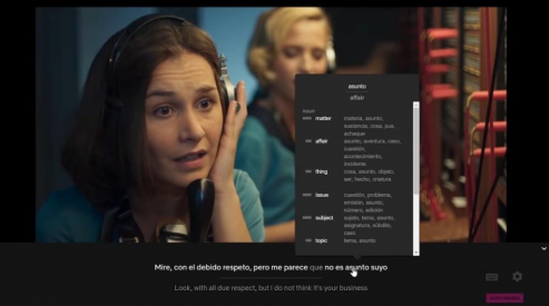 A screenshot from the Spanish show Las Chicas del Cable showing a woman wearing headphones with Spanish subtitles and suggested translations below.